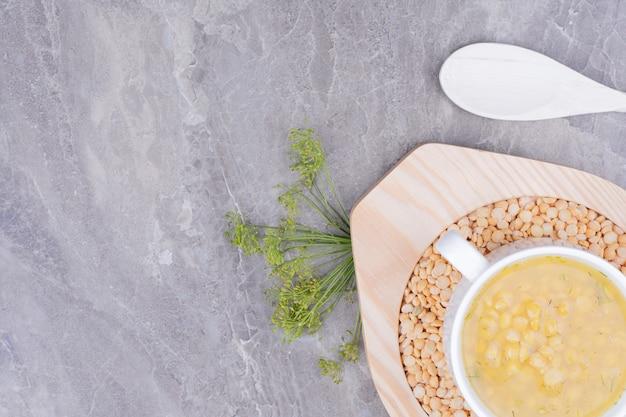 Суп из желтых гороховых бобов в белой чашке на мраморе Бесплатные Фотографии