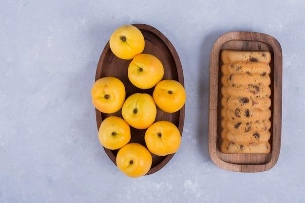 Желтые персики и рулет на деревянных тарелках посреди стола Бесплатные Фотографии