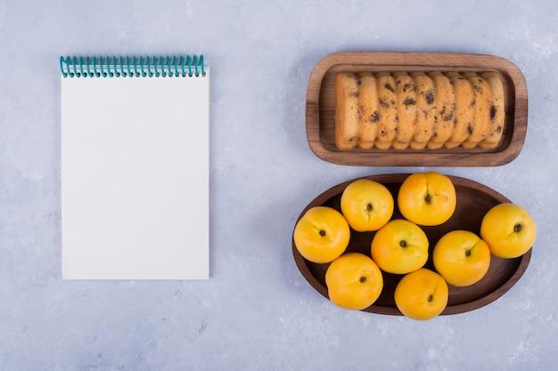 黄色の桃と木製の大皿にロールケーキ、ノートブックを別に 無料写真