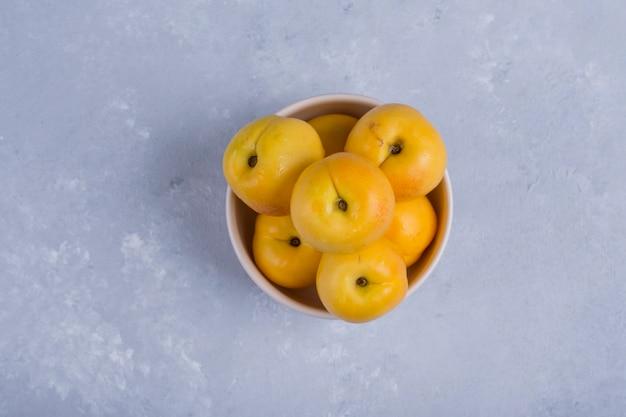 Желтые персики в белой керамической миске посреди стола Бесплатные Фотографии
