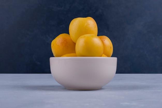 Желтые персики в белой керамической миске, изолированные на синем Бесплатные Фотографии