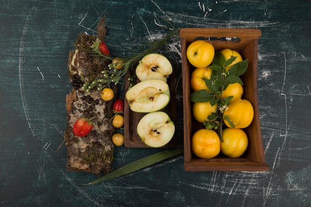 大皿にベリーと木製トレイの黄色い桃 無料写真