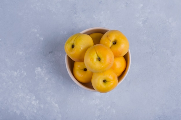 Yellow peaches in a white ceramic bowl in the middle of the table Free Photo