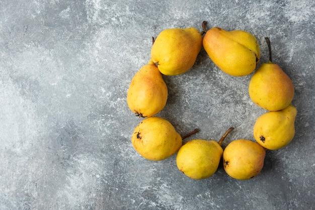 コンクリートの表面に円形の黄色い梨。 無料写真