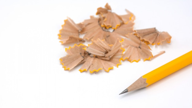 Yellow pencil placed and the sharpener chips on white background Premium Photo