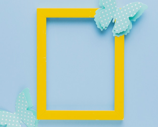 Yellow picture frame decorated with butterfly cutout Free Photo