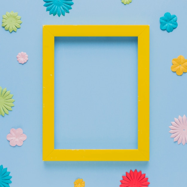 Yellow picture frame surrounded with beautiful flower cutout Free Photo