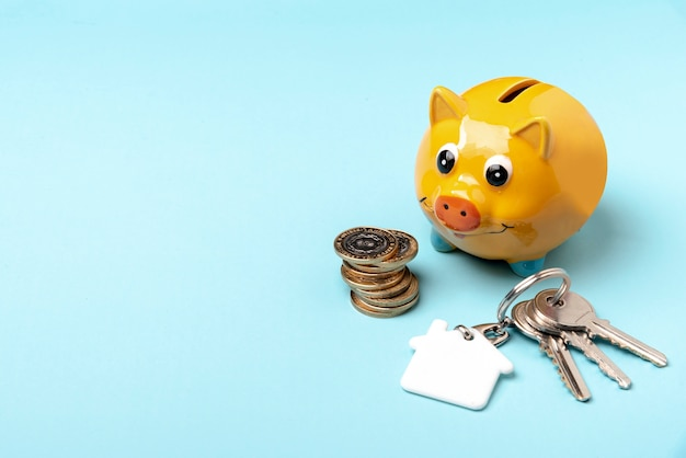 Yellow piggy bank with keys on copy space background Free Photo