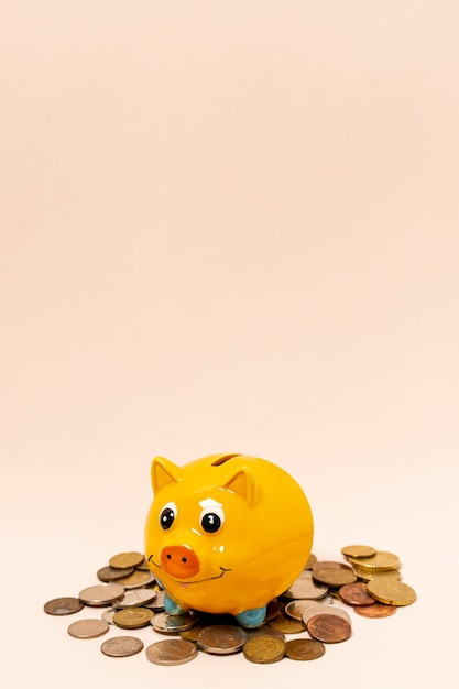 Yellow piggy bank with a stack of coins Free Photo