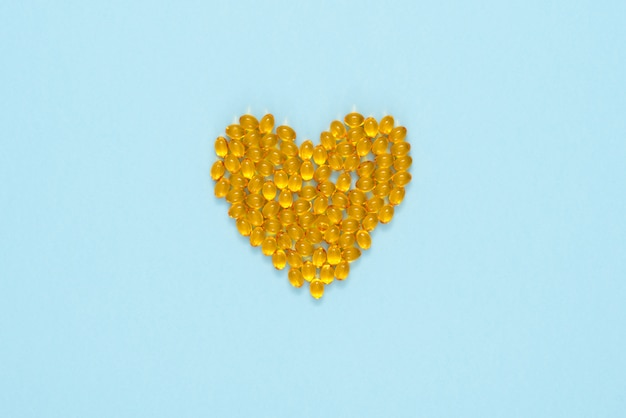 Yellow pills arranged in a shape of heart Premium Photo
