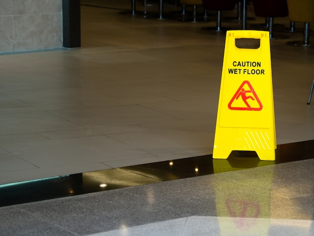 Yellow plastic cone with sign showing warning of wet floor