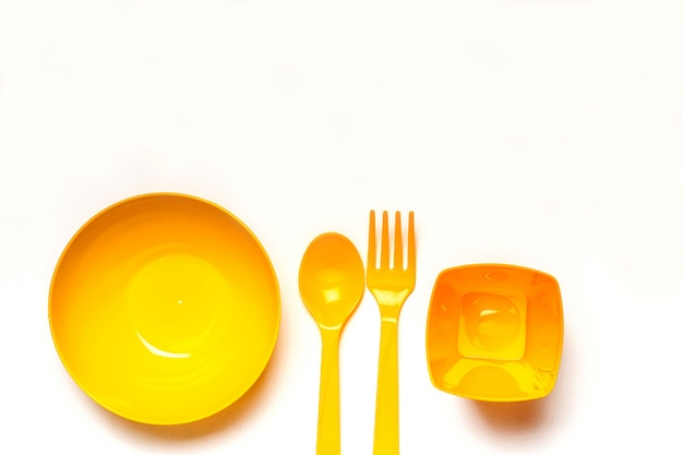 Yellow plastic disposable tableware Premium Photo