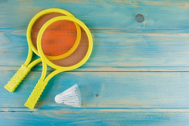 Yellow plastic tennis racket and shuttlecock on blue yellow turquoise desk Free Photo