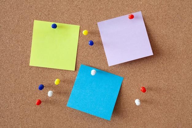 多くのボタンの中でコルクボードに固定されたメモ用紙の黄色、紫、青のシート。ビジネスコンセプトです。 Premium写真