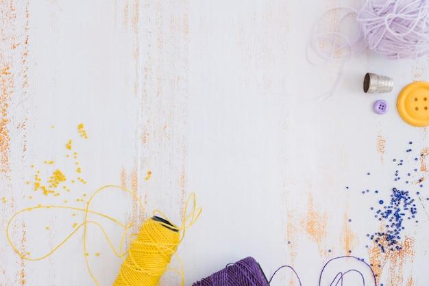 Yellow and purple yarn spool and beads on white desk Premium Photo