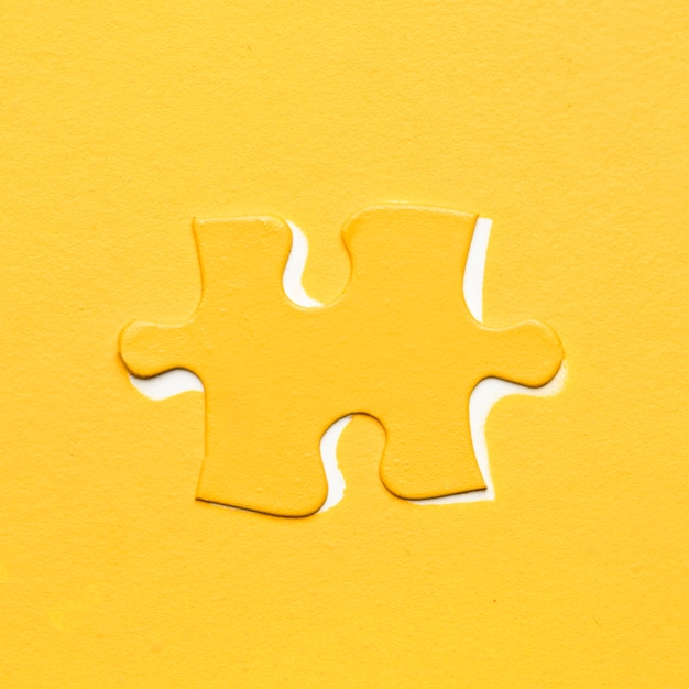 Yellow puzzle piece over colored backdrop Free Photo
