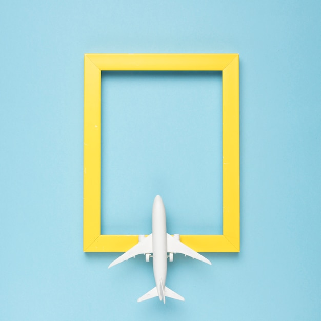 Yellow rectangular empty frame and airplane Free Photo