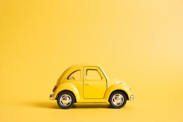 Yellow. retro toy car on yellow. summer travel concept. taxi Premium Photo