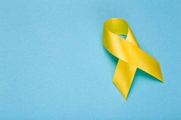 Желтая лента, месяц осведомленности рака детства. рак или лента для предотвращения самоубийств. фон здравоохранения детей. копировать пространство Premium Фотографии