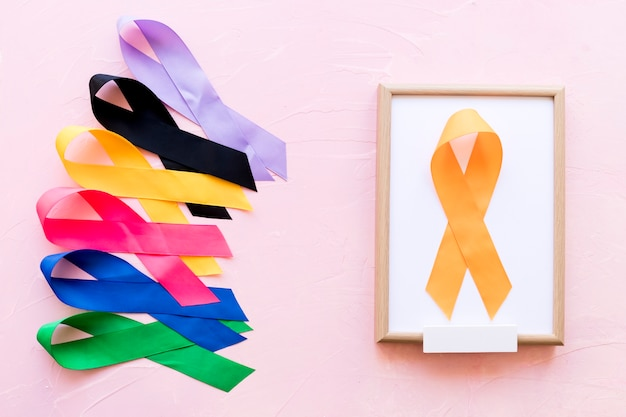 Yellow ribbon on white wooden frame near the row of colorful awareness ribbon Free Photo