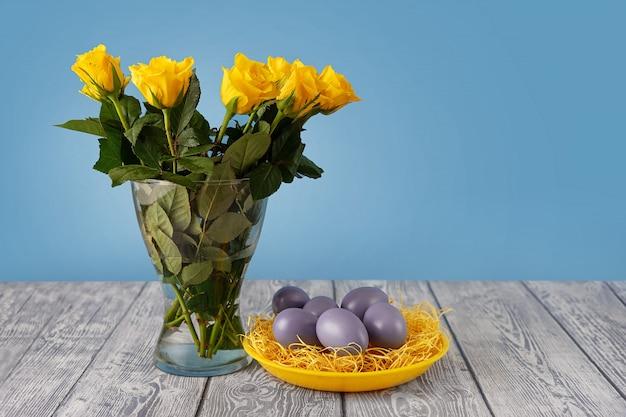 Желтые розы в вазе рядом с желтой тарелкой с синими пасхальными яйцами Premium Фотографии