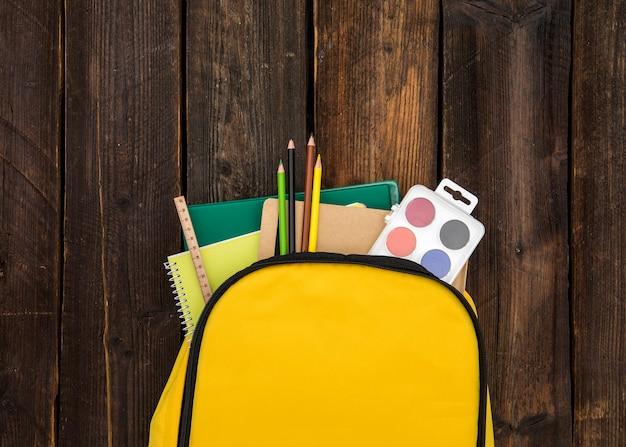 Yellow rucksack with school supplies Free Photo
