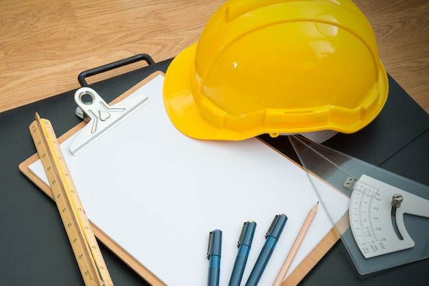 Yellow safety helmet hat and clipboard Premium Photo