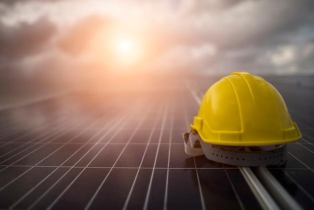 태양 전지 패널에 노란색 안전 헬멧 무료 사진
