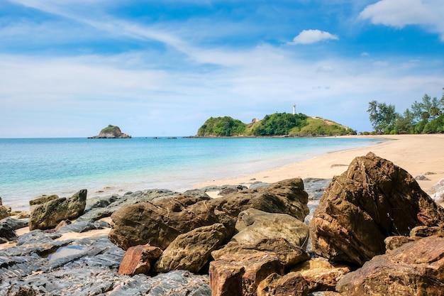 黄色い砂と大きな石、ターコイズブルーの海と空、崖の上の白い灯台 Premium写真