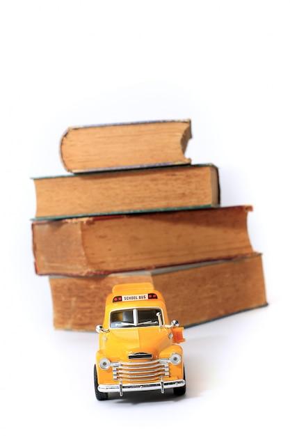 黄色のスクールバスグッズモデルと古い本。ビンテージ背景。 Premium写真
