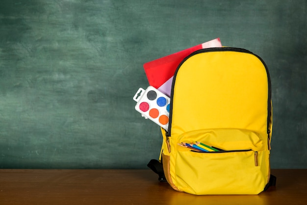 Yellow schoolbag with pencils and paints Premium Photo