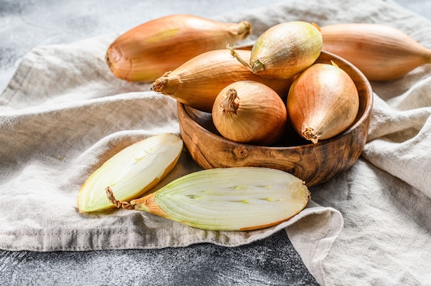 Yellow shallot onions, cut in two halves. gray background. top view Premium Photo