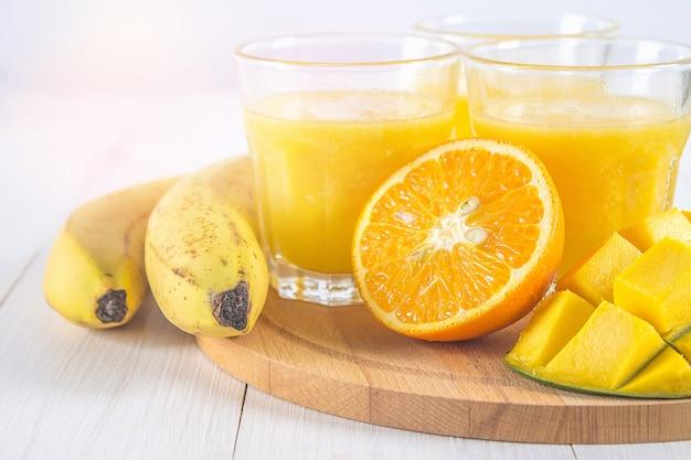 Yellow smoothie of mango, banana and orange on a white wooden table. Premium Photo