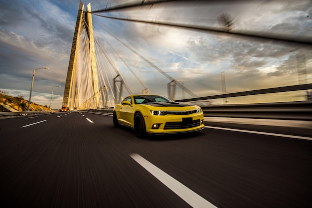 Yellow sport car with black autotuning on the bridge. Free Photo