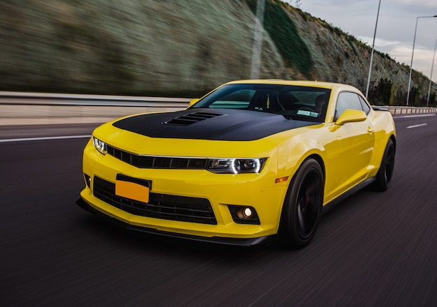 Yellow sport car with black autotuning on the road. Free Photo