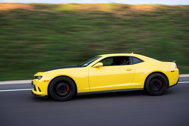 Yellow sport sedan on the road, side view. Free Photo
