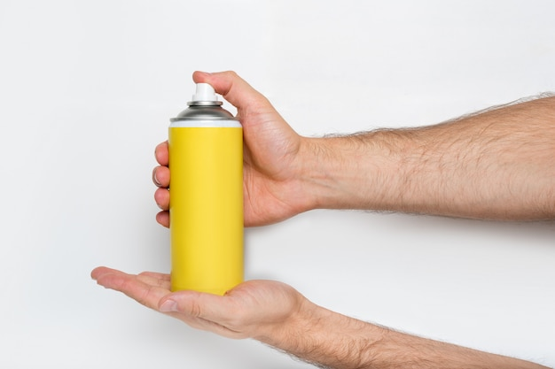 Yellow spray can for spraying in a male hands Premium Photo