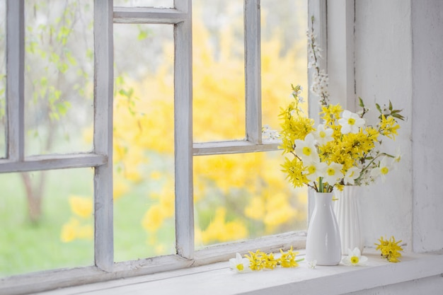 Yellow spring flowers on windowsill Premium Photo