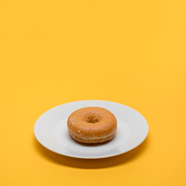 Yellow still life of donut on plate Free Photo