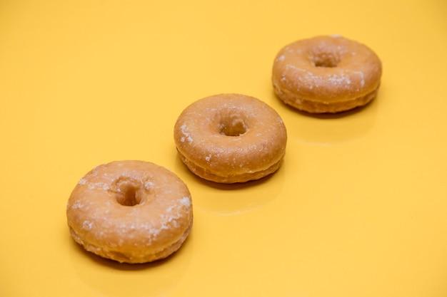 Yellow still life of three donuts Free Photo