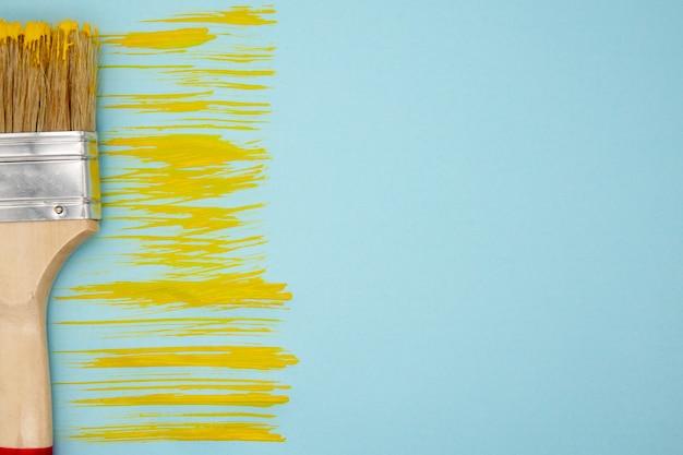 Желтая полоса краски и кисти на синем фоне Premium Фотографии