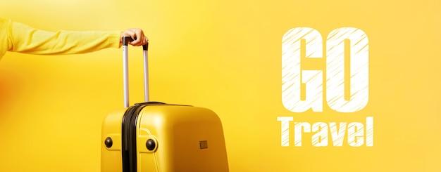 手と碑文の黄色のスーツケースは黄色の壁を越えて旅行、旅行の概念、 Premium写真