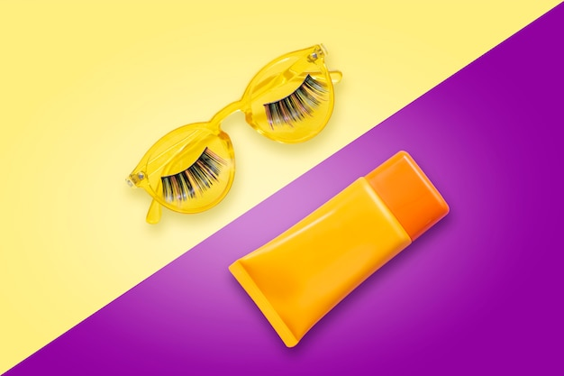 Yellow sunglasses with fake eyelashes and orange sunscreen spf cream on violet background. Premium Photo