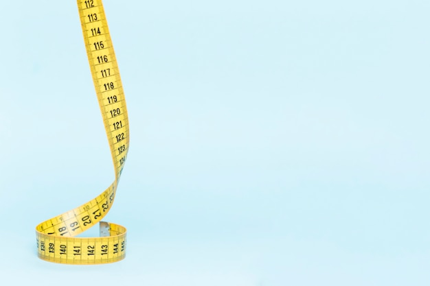 Yellow tape measure on blue background Free Photo
