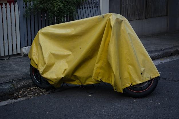 Copertura di tela cerata gialla sopra una motocicletta parcheggiata sulla strada Foto Gratuite