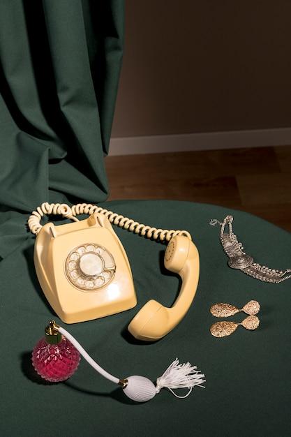 Yellow telephone next to girly items Free Photo