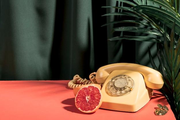 Yellow telephone next to grapefruit on table Free Photo