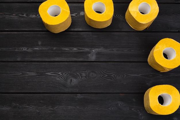 Yellow toilet paper on black wooden background top view Premium Photo