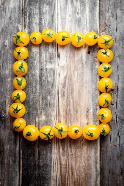 Желтые томаты формируя рамку прямоугольника на темной деревянной предпосылке. вид сверху. Бесплатные Фотографии