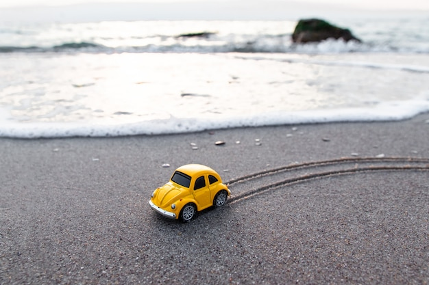 Yellow toy car on the beach in the sunlight in summer. Premium Photo